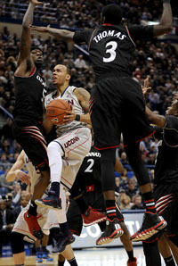 Connecticut Huskies guard Shabazz Napier (13) drives to the hoop as Cincinnati Bearcats forward Justin Jackson (5) and Cincinnati Bearcats forward Shaquille Thomas (3) defend during the second half at the XL Center Saturday afternoon in Hartford.