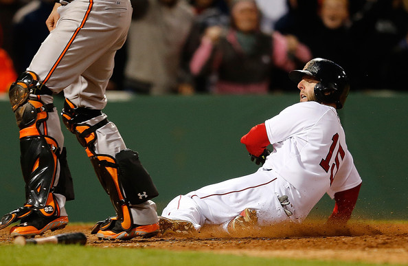 Dustin Pedroia #15 of the Boston Red Sox scores on an errant throw to home against the Baltimore Orioles in the ninth inning to win the game 6-5 at Fenway Park on April 20, 2014 in Boston, Massachusetts.