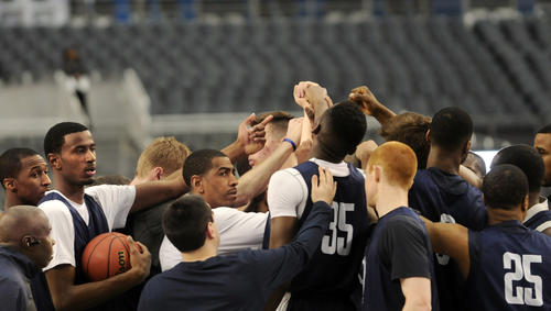 UConn Head Coach Kevin Ollie calls his team into a huddle during practice at the AT&T Stadium Friday.