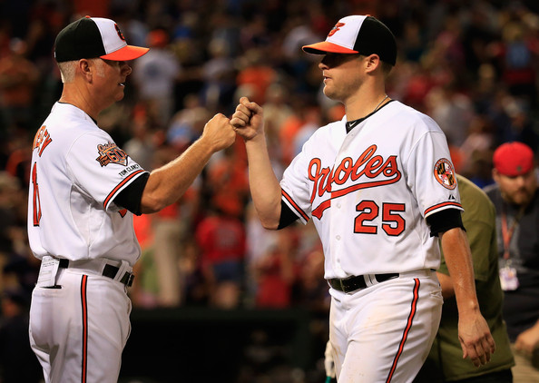 Batting coach Jim Presley #15 congratulates starting pitcher Bud Norris #25 of the Baltimore Orioles following the Orioles 4-0 win over the Boston Red Sox at Oriole Park at Camden Yards on June 9, 2014 in Baltimore, Maryland.