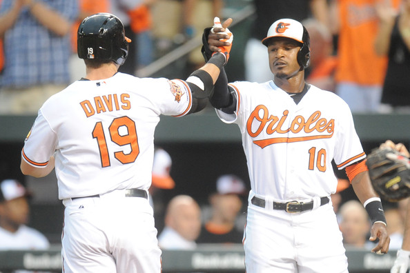 Chris Davis #19 celebrates a two-run home run in the first inning with Adam Jones #10 of the Baltimore Orioles during a baseball game against the Boston Red Sox on June 11, 2014 at Oriole Park at Camden Yards in Baltimore, Maryland.