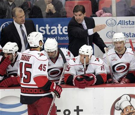 Carolina Hurricanes head coach Peter Laviolette talks to David Tanabe during a break in the third period of their NHL hockey game against the Detroit Red Wings at Joe Louis Arena in Detroit